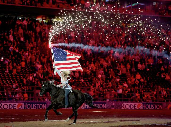 The flag girls circles the arena while the National Anthem is played in the Super Series II rodeo co