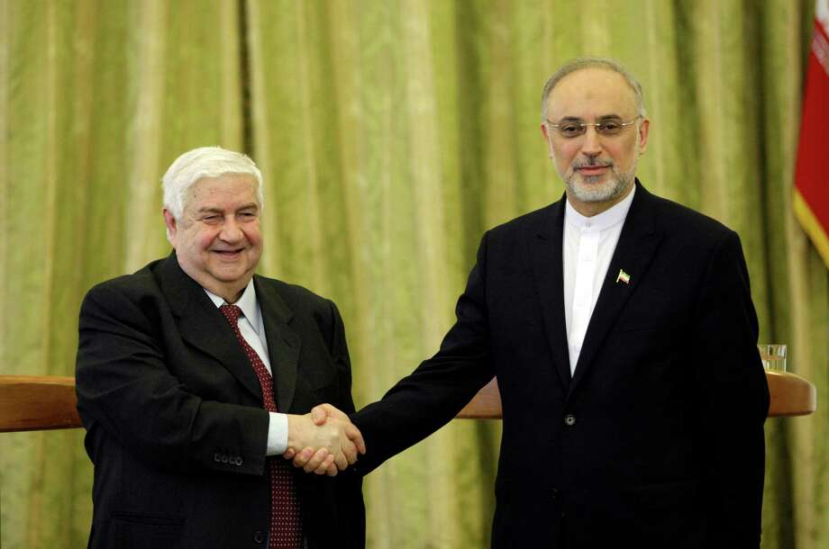 Syrian Foreign Minister Walid al-Moallem, left, and his Iranian counterpart Ali Akbar Salehi, shake hands, at the conclusion of their press conference, in Tehran, Iran, Saturday, March 2, 2013. The Syrian and Iranian foreign ministers on Saturday accused the United States of double standards over the Obama administration's decision to provide aid to rebels fighting to topple President Bashar Assad, saying this will only prolong the conflict. (AP Photo/Vahid Salemi) Photo: Vahid Salemi