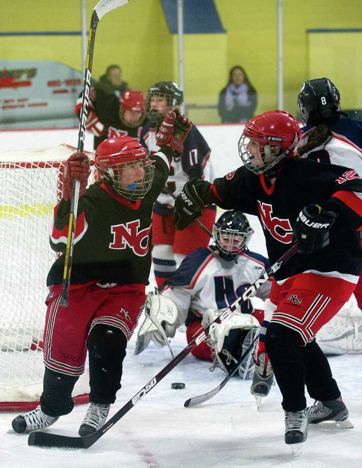 New Canaan's Catherine Granito, left, and Mia Carroll, right, celebrate a goal during Saturday's girls hockey state championship game against Hall-Conard at Terry Connors Rink in Stamford, Conn., on March 2, 2013. Photo: Lindsay Perry / Stamford Advocate