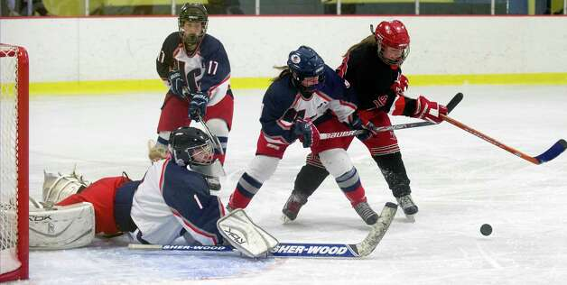 Hall-Conard's Lauren Sorgio, left, dives for the puck as New Canaan's Corbett Ripley tries to get off a shot during Saturday's girls hockey state championship game at Terry Connors Rink in Stamford, Conn., on March 2, 2013. Photo: Lindsay Perry / Stamford Advocate