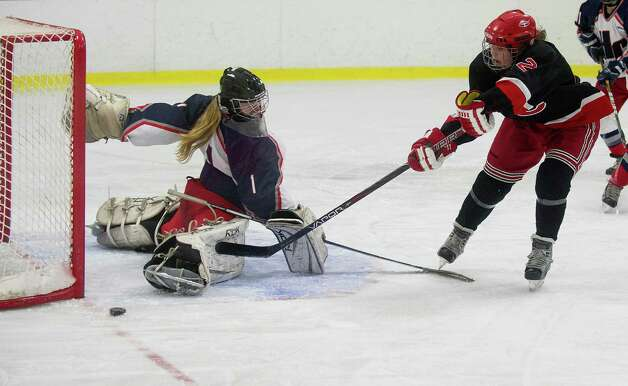 New Canaan's Catherine Granito takes a shot as Hall-Conard's Lauren Sorgio reaches to protect the goal during Saturday's girls hockey state championship game at Terry Connors Rink in Stamford, Conn., on March 2, 2013. Photo: Lindsay Perry / Stamford Advocate