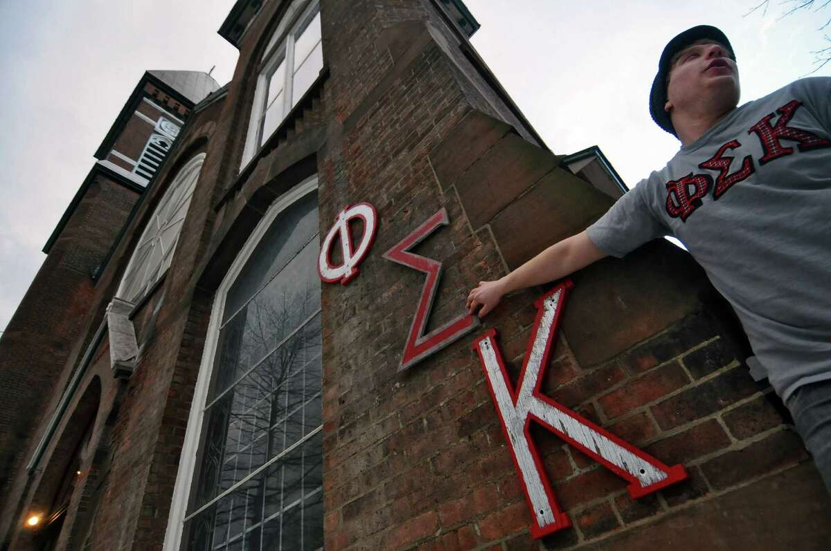 Ori Berger, a senior from Stanford, California, holds a replacement Sigma, a letter from the Greek alphabet, outside of the former St. Francis de Sales church, which was purchased by RPI's Phi Sigma Kappa fraternity from the Roman Catholic Diocese of Albany, in Troy, N.Y., shown here on Monday Feb. 14, 2011. The original Sigma letter placed outside of the church was vandalized. ( Philip Kamrass / Times Union )