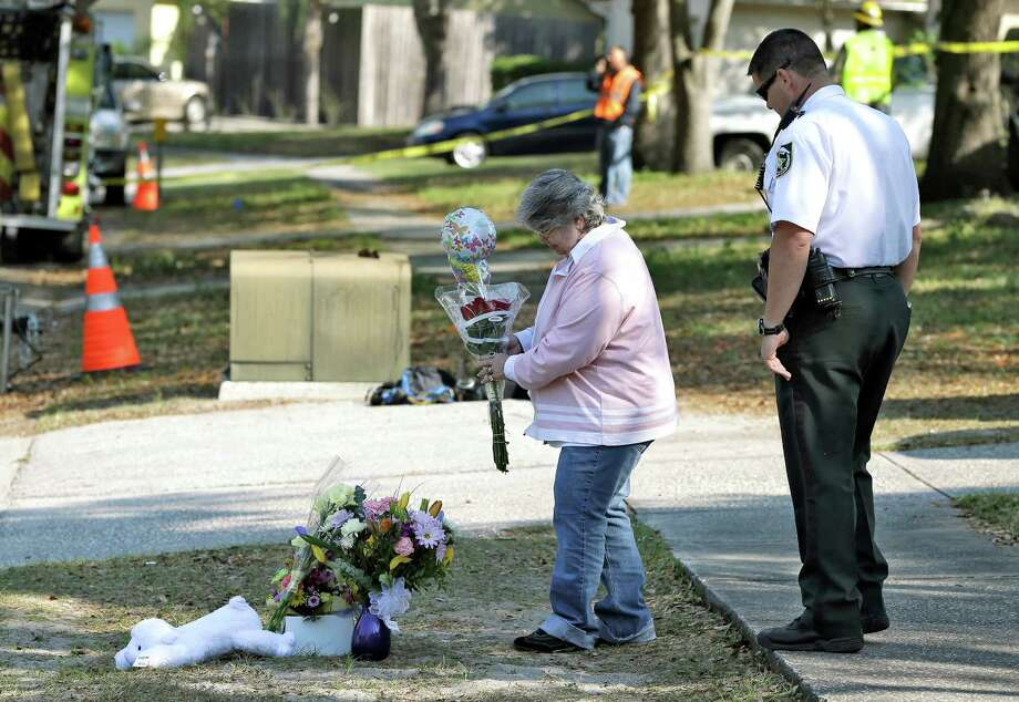 Brenda Bush is escorted by a Hillsborough County Sheriff's deputy as she places flowers, Saturday, March 2, 2013,  at a makeshift memorial in front of a home where a sinkhole opened up underneath a bedroom late Thursday evening and swallowed her son Jeffrey in Seffner, Fla.  Jeffrey Bush, 37, was in his bedroom Thursday night when the earth opened and took him and everything else in his room. Five other people were in the house but managed to escape unharmed. Bush's brother jumped into the hole to try to help, but he had to be rescued himself by a sheriff's deputy. (AP Photo/Chris O'Meara) Photo: Chris O'Meara