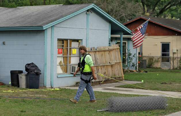 An engineer, tethered with a safety line, walks in front of a home where a sinkhole opened up underneath a bedroom late Thursday evening and swallowed a man in Seffner, Fla. on Saturday, March 2, 2013.   Jeffrey Bush, 37, was in his bedroom Thursday night when the earth opened and took him and everything else in his room. Five other people were in the house but managed to escape unharmed. Bush's brother jumped into the hole to try to help, but he had to be rescued himself by a sheriff's deputy.  (AP Photo/Chris O'Meara) Photo: Chris O'Meara