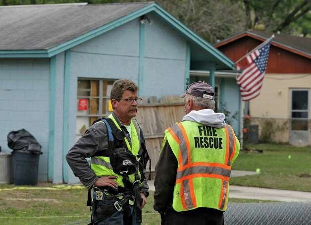 Engineers talk in front of a home, where a sinkhole opened up underneath a bedroom late Thursday evening and swallowed a man, in Seffner, Fla. on Saturday, March 2, 2013.   Jeffrey Bush, 37, was in his bedroom Thursday night when the earth opened and took him and everything else in his room. Five other people were in the house but managed to escape unharmed. Bush's brother jumped into the hole to try to help, but he had to be rescued himself by a sheriff's deputy.  (AP Photo/Chris O'Meara) Photo: Chris O'Meara