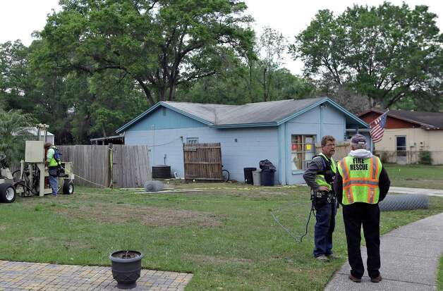Engineers talk in front of a home where a sinkhole opened up underneath a bedroom late Thursday evening and swallowed a man, Saturday, March 2, 2013 in Seffner, Fla.  Jeff Bush, 37, was in his bedroom Thursday night when the earth opened and took him and everything else in his room. Five other people were in the house but managed to escape unharmed. Bush's brother jumped into the hole to try to help, but he had to be rescued himself by a sheriff's deputy. (AP Photo/Chris O'Meara) Photo: Chris O'Meara