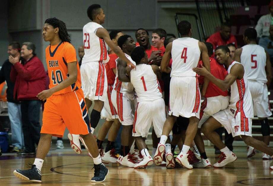 Bush forward Myles Rice walks off the court as Travis players celebrate. Photo: Smiley N. Pool, Houston Chronicle / © 2013  Houston Chronicle