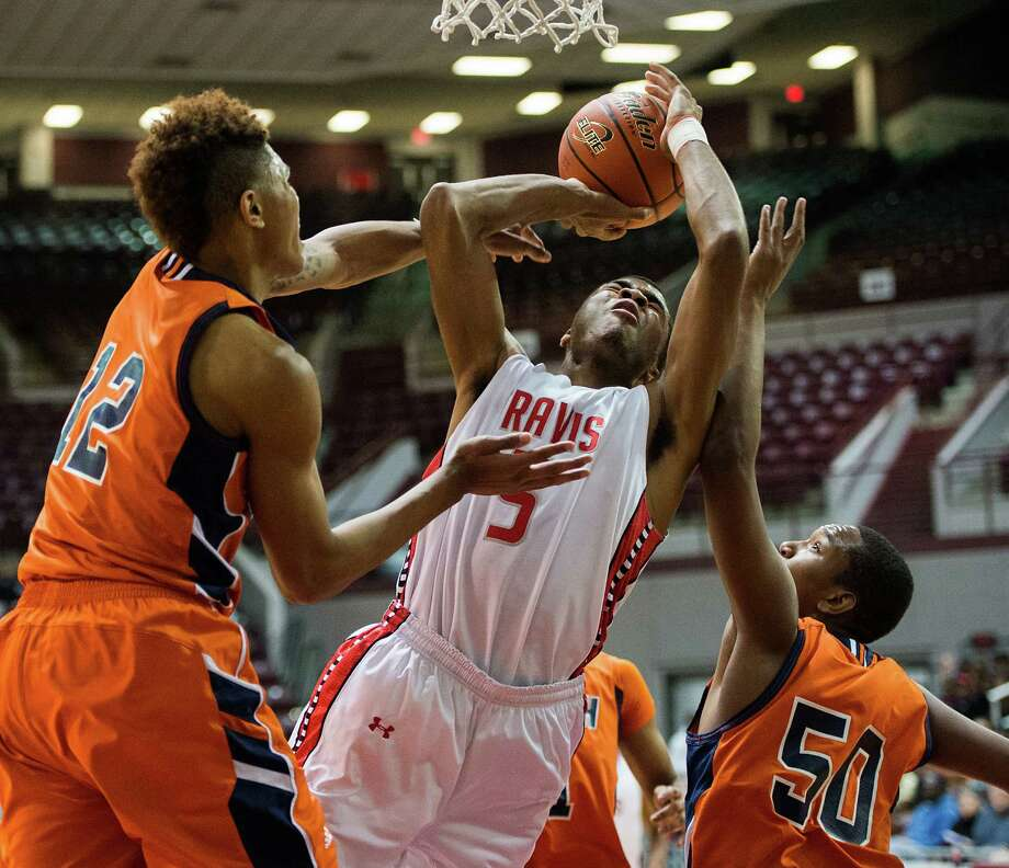 Travis guard Andrew Harrison drives to the basket between Bush guard Kelly Oubre (12) and forward Ladarius Johnson (50). Photo: Smiley N. Pool, Houston Chronicle / © 2013  Houston Chronicle