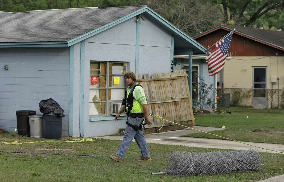 An engineer, tethered with a safety line, walks in front of a Seffner, Fla., home where a sinkhole swallowed Jeff Bush, 37. The four-bedroom house will be demolished. Photo: Chris O'Meara / Associated Press