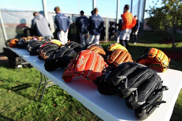 Astros players line up to look at the new Rawlings  gloves on display during spring training workouts at Osceola County Stadium in Kissimmee, Fla. Photo: Karen Warren / © 2013 Houston Chronicle