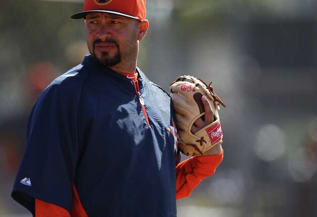 Astros bullpen catcher Javier Bracamonte breaks in pitcher Alex White's glove. Photo: Karen Warren / © 2013 Houston Chronicle