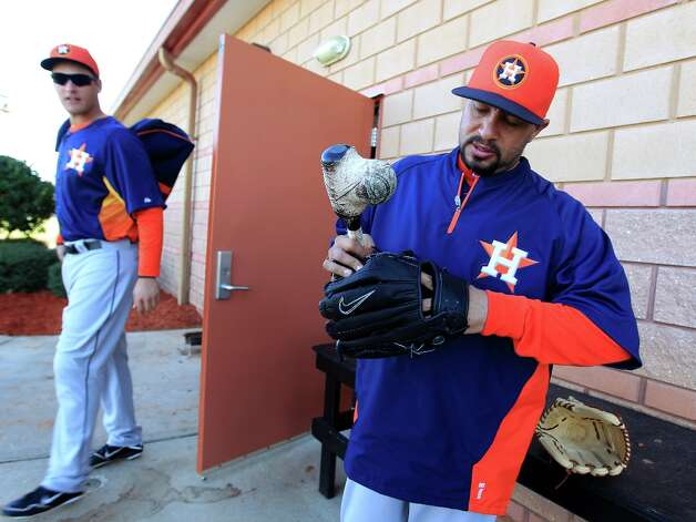 Astros bullpen catcher Javier Bracamonte uses a small bat with a ball taped to it as he breaks in gloves. Photo: Karen Warren / © 2013 Houston Chronicle