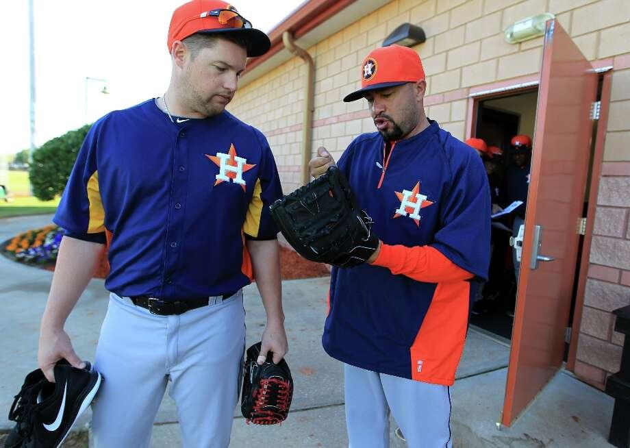 Astros bullpen catcher Javier Bracamonte talks with pitcher Bud Norris, left, about breaking in gloves. Photo: Karen Warren / © 2013 Houston Chronicle