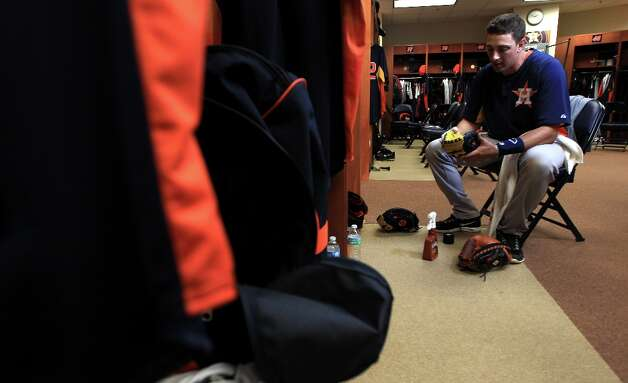 Astros catcher Jason Castro works on breaking in his new gloves in the clubhouse. Photo: Karen Warren / © 2013 Houston Chronicle