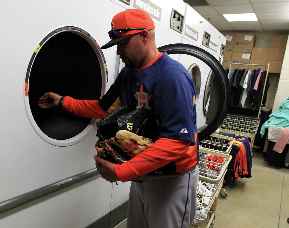 Astros bullpen catcher Javier Bracamonte puts gloves into the dryer in the clubhouse as he breaks in several players gloves. Photo: Karen Warren / © 2013 Houston Chronicle