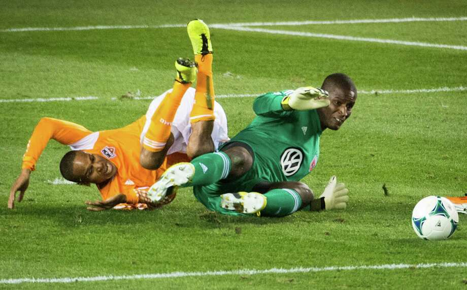 Dynamo midfielder Ricardo Clark (13) tumbles over D.C. United goalkeeper Bill Hamid. Photo: Smiley N. Pool, Houston Chronicle / © 2013  Houston Chronicle