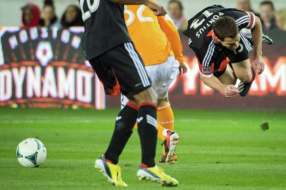 D.C. United midfielder Chris Pontius (13) is upended in a collision with Dynamo defender Bobby Boswell. Photo: Smiley N. Pool, Houston Chronicle / © 2013  Houston Chronicle
