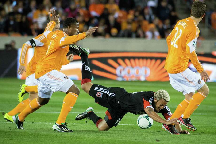 D.C. United midfielder Nick DeLeon (18) hits the turf as he collides with Houston Dynamo defender Jermaine Taylor (4) during the first half of a MLS soccer match on Saturday, March 2, 2013, at BBVA Compass Stadium in Houston. Photo: Smiley N. Pool, Houston Chronicle / © 2013  Houston Chronicle
