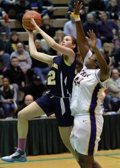 Holy Names' #32 Hannah Friend, left,drives to the basket past Troy's #44 Cheyenne Williams during th