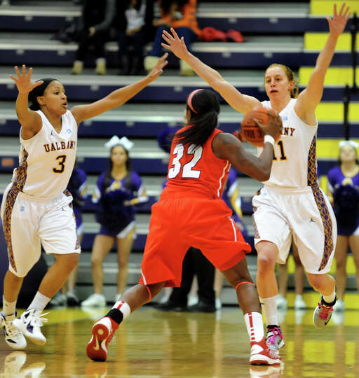 UAlbany's Margarita Rosario (3), left, and Julie Forster (11), right, defend against Stony Brook's C