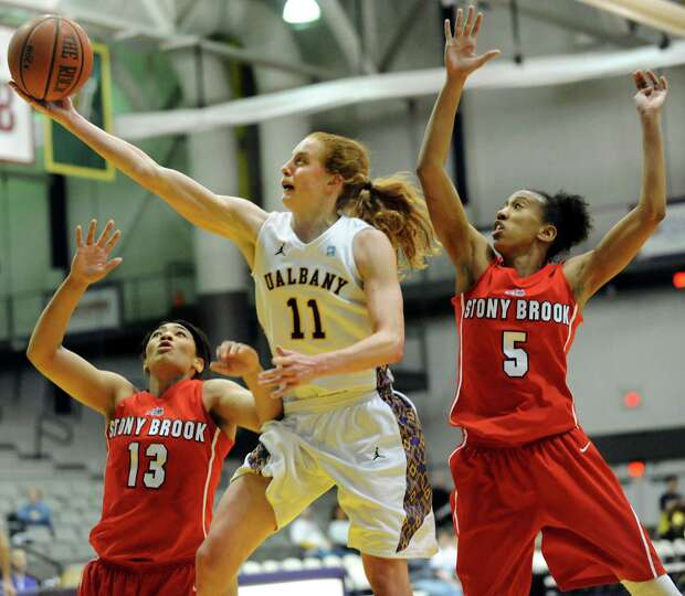UAlbany's Julie Forster (11), center, goes to the hoop against Stony Brook's Sabre Proctor  (13), le