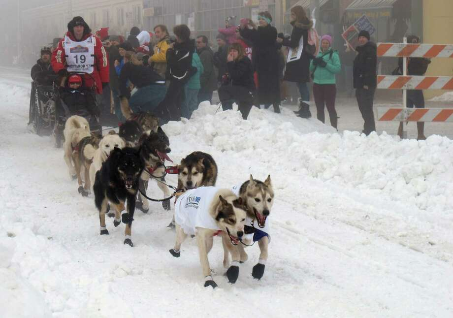 Defending champion Dallas Seavey takes off Saturday, March 2, 2013, in downtown Anchorage, Alaska, for the ceremonial start of the 2013 Iditarod Trail Sled Dog Race. The race, which will take mushers and dog teams about a thousand miles across the Alaska wilderness, starts Sunday, March 3, 2013, in Willow, Alaska. (AP Photo/Mark Thiessen) Photo: Mark Thiessen