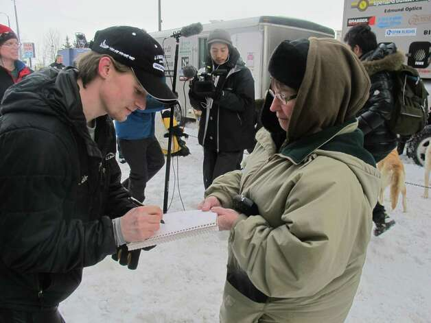 Defending champion Dallas Seavey, left, signs an autograph for Bunky Nistler of Beach, N.D., before the ceremonial start of the 2013 Iditarod Trail Sled Dog Race in Anchorage, Alaska on Saturday, March 2, 2013. The race, which will take mushers about a thousand miles across the Alaska wilderness, starts Sunday, March 3, 2013, in Willow, Alaska. (AP Photo/Mark Thiessen) Photo: Mark Thiessen