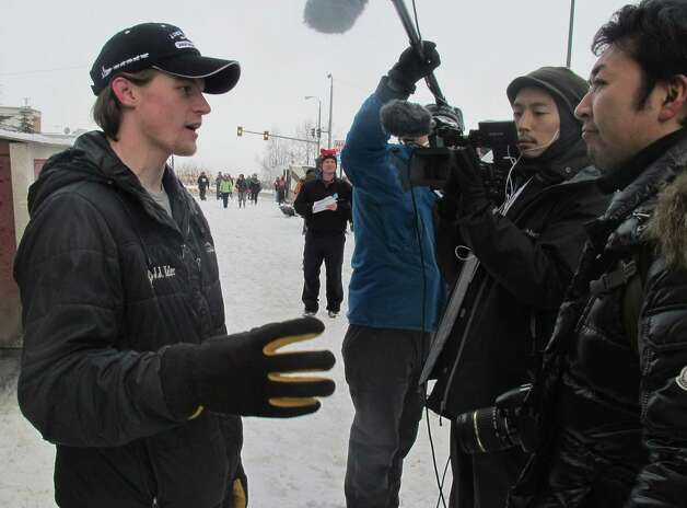 Defending champion Dallas Seavey, left, is interviewed by Japanese media before the ceremonial start of the 2013 Iditarod Trail Sled Dog Race in Anchorage, Alaska on Saturday, March 2, 2013. The race, which will take mushers about a thousand miles across the Alaska wilderness, starts Sunday, March 3, 2013, in Willow, Alaska. (AP Photo/Mark Thiessen) Photo: Mark Thiessen