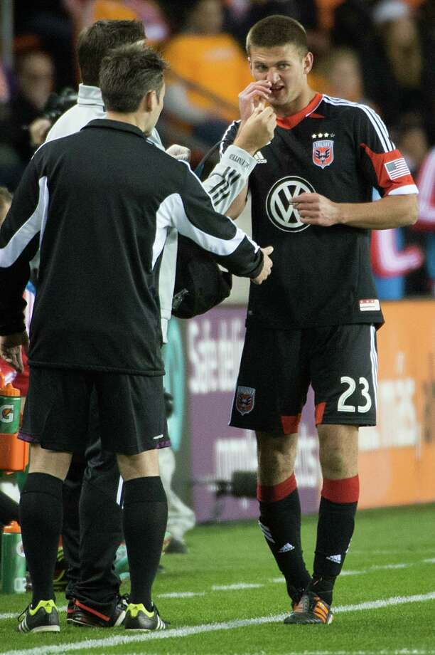 D.C. United midfielder Perry Kitchen (23) is treated for a bloody nose. Photo: Smiley N. Pool, Houston Chronicle / © 2013  Houston Chronicle