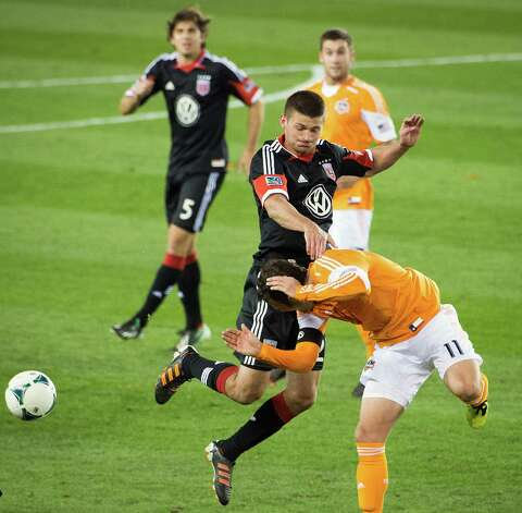 Dynamo midfielder Brad Davis (11) collides with D.C. United midfielder Perry Kitchen. Photo: Smiley N. Pool, Houston Chronicle / © 2013  Houston Chronicle