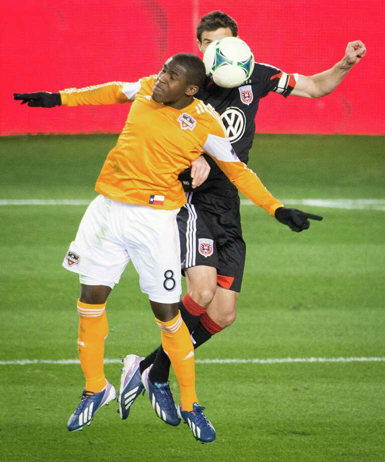 Dynamo defender Kofi Sarkodie (8) fights for a header against D.C. United midfielder Chris Pontius. Photo: Smiley N. Pool, Houston Chronicle / © 2013  Houston Chronicle
