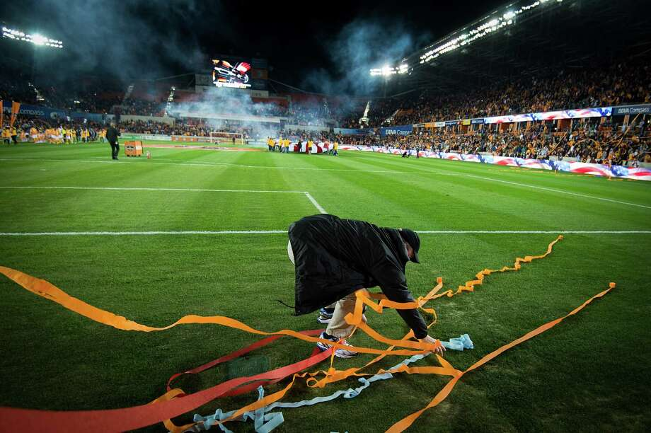 A stadium official collects streamers tossed onto the field by fans. Photo: Smiley N. Pool, Houston Chronicle / © 2013  Houston Chronicle