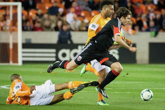 D.C. United defender Dejan Jakovic (5) leaps over Dynamo midfielder Ricardo Clark. Photo: Smiley N. Pool, Houston Chronicle / © 2013  Houston Chronicle