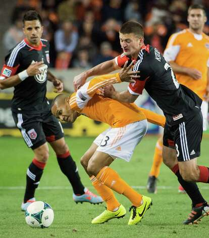 Dynamo midfielder Ricardo Clark (13) tangles with D.C. United midfielder Perry Kitchen. Photo: Smiley N. Pool, Houston Chronicle / © 2013  Houston Chronicle