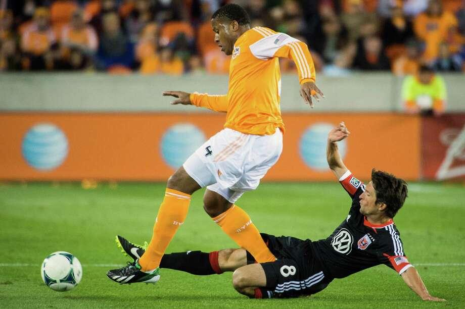 D.C. United midfielder John Thorrington (8) makes a sliding tackle against Dynamo defender Jermaine Taylor. Photo: Smiley N. Pool, Houston Chronicle / © 2013  Houston Chronicle