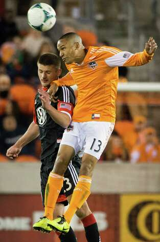Dynamo midfielder Ricardo Clark (13) wins a header from D.C. United midfielder Perry Kitchen. Photo: Smiley N. Pool, Houston Chronicle / © 2013  Houston Chronicle