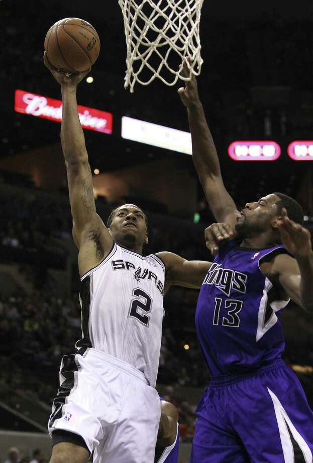 Kawhi Leonard, driving on Sacramento guard Tyreke Evans in Friday's win, says only an offseason of rest will make his left quad tendinitis 100 percent. Photo: Kin Man Hui / San Antonio Express-News