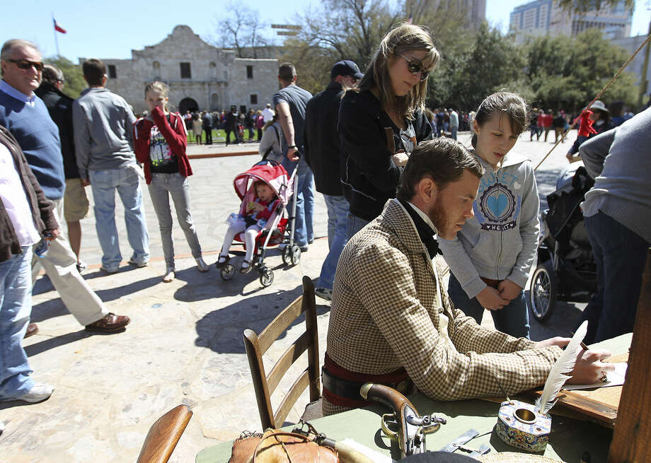 Erik McBroom (seated), portraying Alamo commander William Barret Travis, shows Cherann Sylvester and her daughter Carson how people communicated in the 1800s during the Alamo Heritage Interpretation. McBroom was joined by other historians at Alamo Plaza to educate and enlighten visitors as the city celebrated the 177th anniversary of the state's independence day. Photo: Photos By Kin Man Hui / San Antonio Express-News