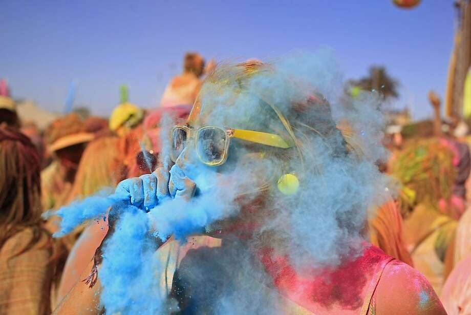 A woman blows blue paint powder on to her friend during the holi one colour Festival held in the city of Cape Town, South Africa, Saturday, March 2, 2013. Thousands of people are taking part in the festival by throwing coloured paint powder at each other to express freedom and the colour of everyday life. Photo: Schalk Van Zuydam, Associated Press