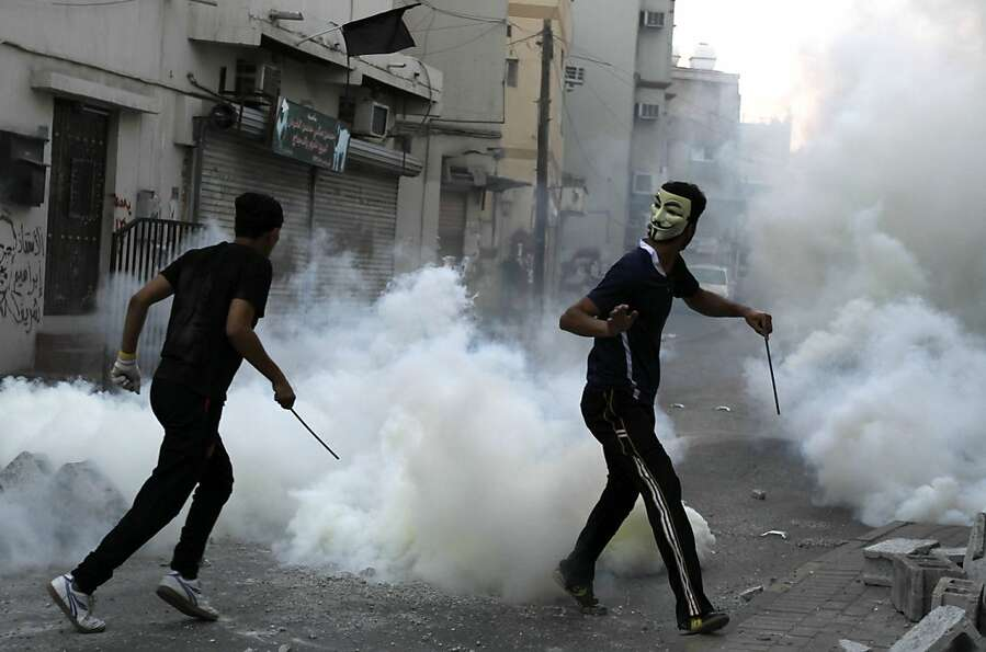 Bahraini anti-government protesters carry steel rods into clashes with riot police firing tear gas a