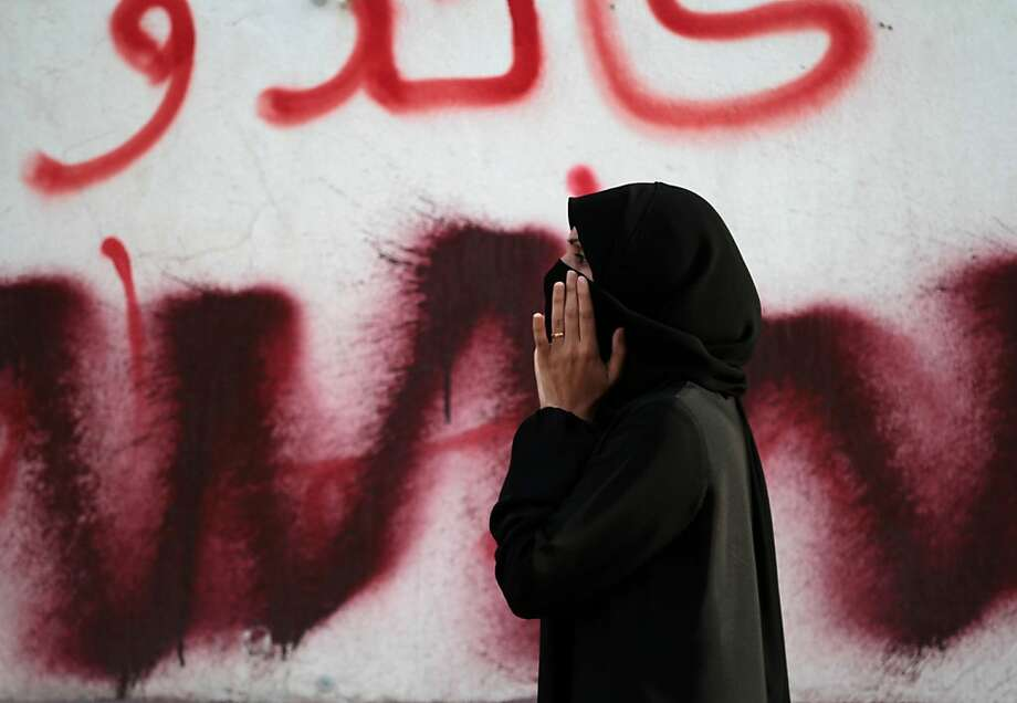 A Bahraini anti-government protester standing in front of anti-government graffiti that has been partly painted over shouts toward riot police during clashes in Manama, Bahrain, on Saturday, March 2, 2013. Protesters tried to march on the country's heavily guarded main public hospital, saying they intended to retrieve the body of a protester who died last week. The body of Mahmoud al-Jazeeri, 20, has not yet been released for burial because of a dispute between the family and the government over funeral plans. Photo: Hasan Jamali, Associated Press