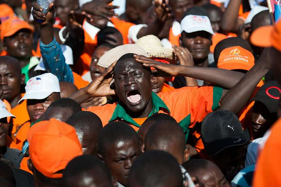 A Kenyan man gestures during a push in a cramped crowd at a rally for Kenyan Prime Minister and pres