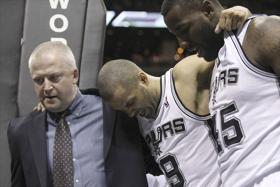 Spurs guard Tony Parker (center) is helped off the court by trainer Will Sevening (left) and DeJuan Blair on Friday night after suffering a Grade 2 left ankle sprain against the Kings. Photo: Kin Man Hui / San Antonio Express-News