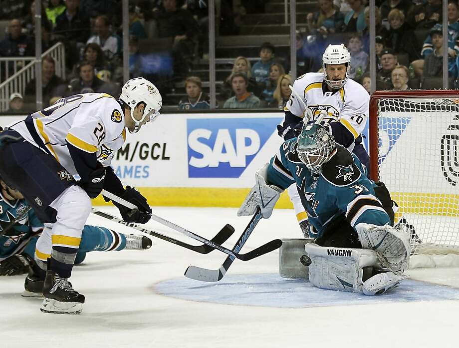 Sharks goalie Antti Niemi makes one of his 18 saves, denying Paul Gaustad (left) as the Predators' Richard Clune watches. Photo: Tony Avelar, Associated Press
