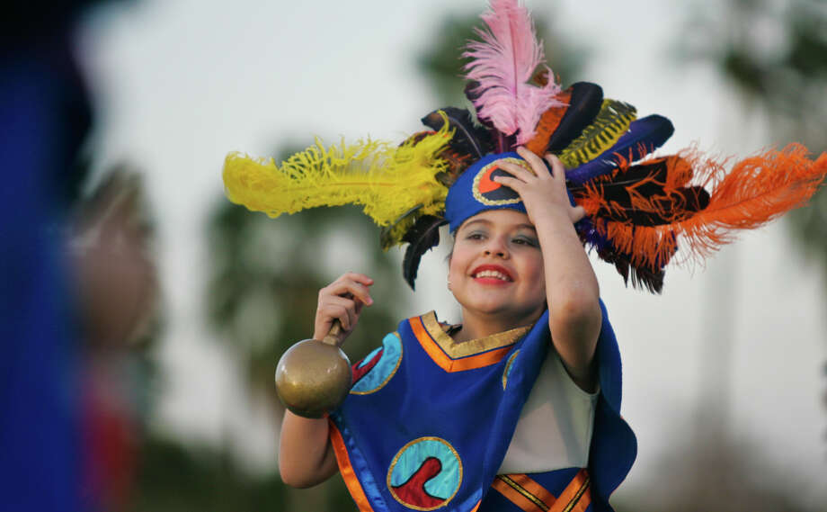 In this Monday, Feb. 25, 2013 photo, Cynthia Cantu struggles with her headpiece through her dances during Brownsville Independent School District's annual Fiesta Folklorica at Sams Memorial Stadium in Brownsville, Texas. Several schools participated in the event that celebrated music and dances from Mexico. Photo: Yvette Vela, AP Photo/The Brownsville Herald / The Brownsville Herald