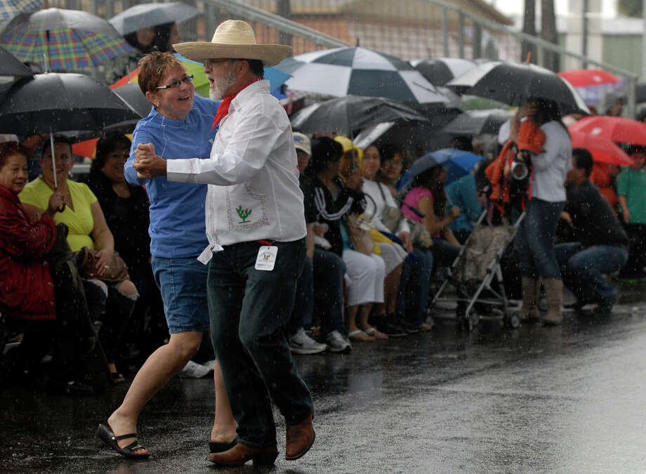 A couple does a a traditional Mexican dance in the rain at the annual Charro Days Festival on Sunday, Feb. 24, 2013, in Brownsville. Photo: Brad Doherty, AP Photo/The Brownsville Herald / Brownsville Herald