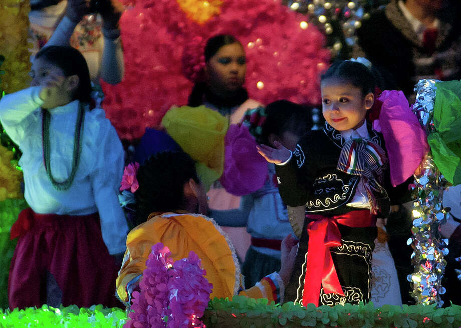 A young girl waves from the Faith Christian Academy float during the Charro Days Illuminated Parade on Friday, March 1, 2013 along Elizabeth Street in Brownsville. Photo: Paul Chouy, AP Photo/The Brownsville Herald / The Brownsville Herald
