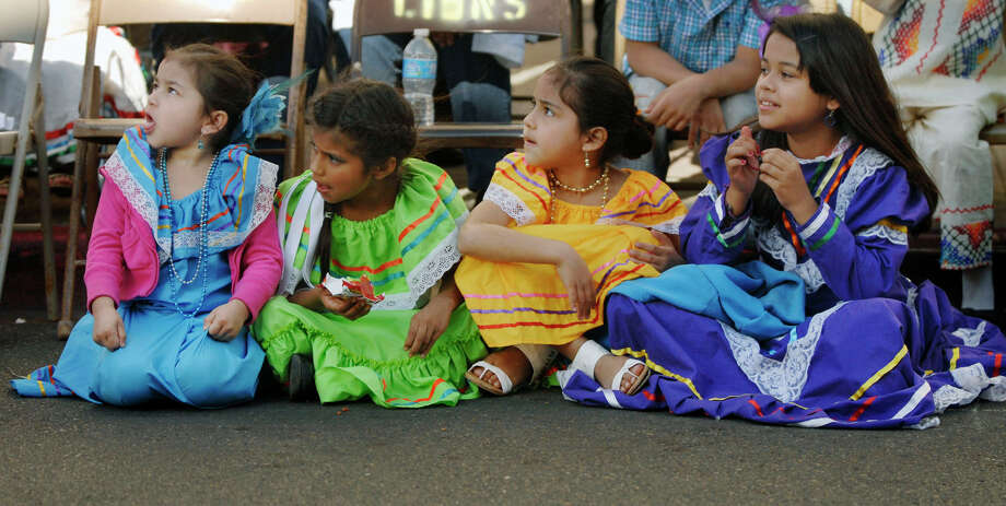 In this Feb. 28, 2013 photo, four little girls dressed in their traditional dresses look down Elizabeth St. in anticipation of the Charro Days parade as it approached the area they were seated in Brownsville, Texas. The 76th Annual Charro Days in underway in Brownsville with school children featured in the Children's Parade on Thursday. Photo: Brad Doherty, AP Photo/The Brownsville Herald / BROWNSVILLE HERALD