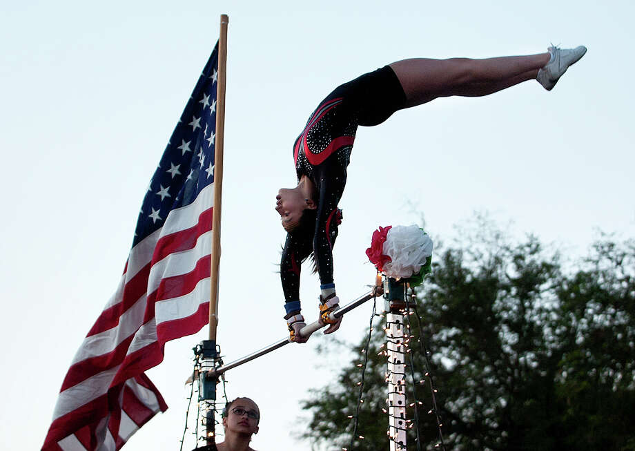 A gymnast performs on the Gionastics float during the Charro Days Illuminated Parade on Friday, March 1, 2013 along Elizabeth Street in Brownsville. Photo: Paul Chouy, AP Photo/The Brownsville Herald / The Brownsville Herald