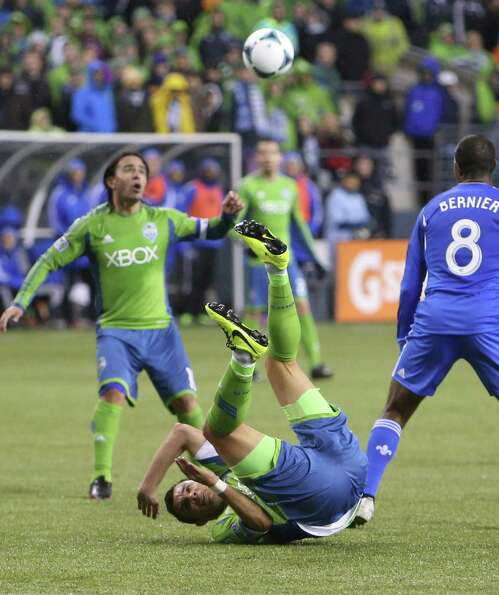Seattle Sounders player Sammy Ochoa goes upside down as he loses control of the ball against the Mon